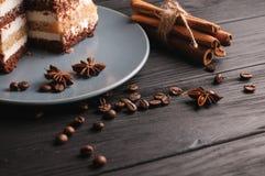 Tiramisu doux de dessert dans une coupe d'un plat gris sur un fond en bois noir avec des épices : bâtons de cannelle et badan Photos libres de droits