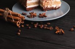 Tiramisu doux de dessert dans une coupe d'un plat gris sur un fond en bois noir avec des épices : bâtons de cannelle et badan Photographie stock libre de droits