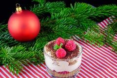 Tiramisu with fresh raspberries as a dessert for Christmas dinne. R. A portion of tiramisu, red Christmas ball  and pine branches on a table Stock Image