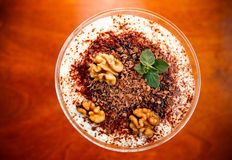 Tiramisu. In glass decorated by walnut on wooden table Stock Photo