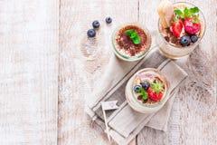 Tiramisu italien fait maison de dessert avec les fraises, la menthe et le cacao dans des pots en verre Photographie stock libre de droits