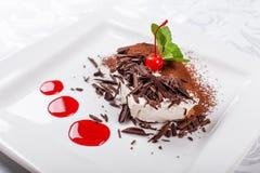 Tiramisu Klassiek Dessert met cacao en chocolade op witte vierkante plaat Versierd met Kers en Munt Zoet royalty-vrije stock afbeelding