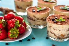 tiramisu luxueux de dessert dans un verre sur un fond bleu décoré de la menthe et des fraises Photos libres de droits