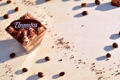 Tiramisu mały szkło, kawowe fasole, kakaowy proszek, czekoladowi kawałki z ciepłym spadkiem barwi w ostrości w tle Obrazy Royalty Free