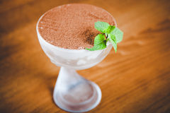 Tiramisu. In a matte glass cup with a green mint leaf Royalty Free Stock Photography