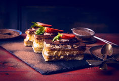 Tiramisu med jordgubbar på mörk träbakgrund Fotografering för Bildbyråer