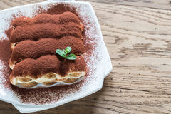 Tiramisu on the plate on the wooden background Royalty Free Stock Images