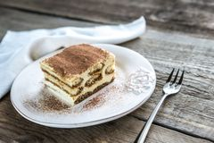 Tiramisu on the plate on the wooden background Stock Photos