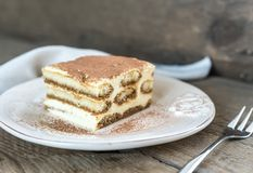 Tiramisu on the plate on the wooden background Stock Images
