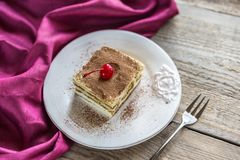 Tiramisu on the plate on the wooden background Stock Photography
