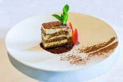 Tiramisu Espresso Dessert on a Big Plate White Tablecloth Topped with Mint and Strawberry royalty free stock photography