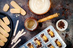 Tiramisu popsicles making. Ice pops with italian savoiardi cookies and tiramisu ingredients on rustic kitchen table. Top view Royalty Free Stock Photos
