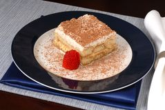 Tiramisu with sliced strawberry on a blue plate. A piece of delicious tiramisu with sliced strawberry on a blue plate Royalty Free Stock Images