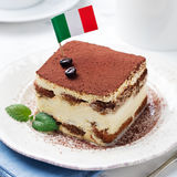 Tiramisu, sobremesa italiana tradicional em uma placa branca com bandeira italiana Imagem de Stock Royalty Free