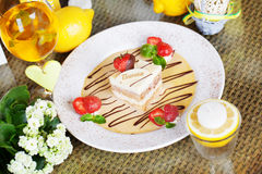 Tiramisu with strawberries on a plate lemon letter serving table Royalty Free Stock Photo