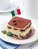 Tiramisu, traditional Italian dessert on a white plate with Italian flag Stock Photos