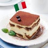 Tiramisu, traditional Italian dessert on a white plate with Italian flag Royalty Free Stock Image