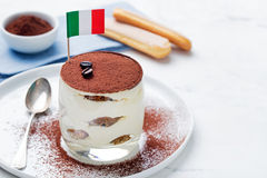 Tiramisu, traditional Italian dessert on a white plate with Italian flag Stock Photos