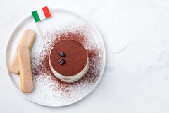Tiramisu, traditional Italian dessert on a white plate with Italian flag Top view Copy space.  royalty free stock photography