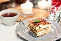 tiramisu by candlelight, romantic date in Italy, tiramisu dessert on a porcelain plate royalty free stock photography