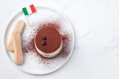 Tiramisu traditionell italiensk efterrätt på en vit platta med italienskt utrymme för kopia för bästa sikt för flagga royaltyfri fotografi