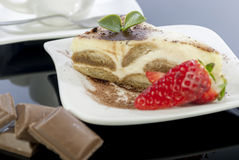 Tiramisu on wood table. Italian desert tiramisu with coffe and strawberry on wood table stock image