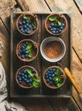 Tiramisu y tamiz hechos en casa con el polvo de cacao en bandeja de madera Imagenes de archivo