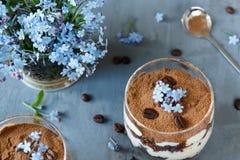 Tiramisuen i ett exponeringsglas, blått blommar glömma-mig-nots Royaltyfri Fotografi