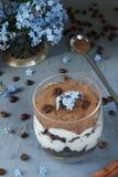 Tiramisuen i ett exponeringsglas, blått blommar glömma-mig-nots Royaltyfria Foton