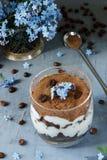 Tiramisuen i ett exponeringsglas, blått blommar glömma-mig-nots Fotografering för Bildbyråer
