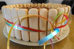 Tiramisufödelsedagkaka med ljusbruna kakasockerkaksbit i form av ett finger royaltyfri bild