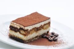 Tiramisukuchen mit Kakaopulver und Kaffeebohnen auf weißer Platte, Fotografie für Konditorei, Schwammkuchen Lizenzfreies Stockfoto