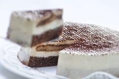 Tiramisutörtchen auf Metalllöffel, Kakaopulver auf Kuchen, Geburtstagskuchen auf weißer Platte, Konditorei, Fotografie für Shop Stockbilder