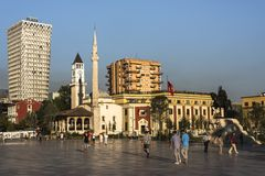 TIRANA, ALBANIA - AUGUST 1, 2017: Locals at Skanderbeg Square in the early evening in front of the Plaza Hotel, Et`hem Bey Mosque stock image