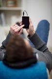 Tirante adolescente moderno che per mezzo del giocatore mp3 Fotografia Stock