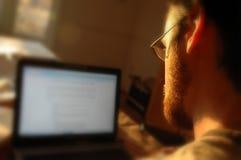 Tirante al suo computer portatile Fotografie Stock