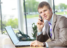 Tirante bello di affari che lavora al cellulare ed al giro Fotografia Stock