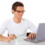 Tirante casuale che installa software sul suo computer portatile Fotografia Stock Libera da Diritti