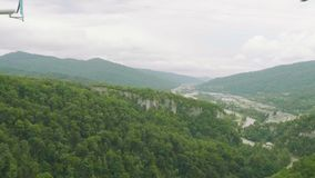 Tirante com mola do arranha-céus para dois pessoas em montanhas verdes Panorama de um vale da montanha video estoque
