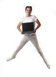Tirante felice di salto con il computer portatile isolato su bianco Fotografia Stock