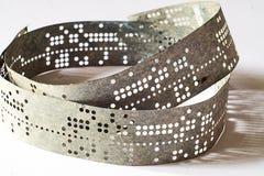 Tiras de cinta perforada vieja en una superficie blanca imagen de archivo libre de regalías