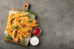 Tiras empanadas del pollo con dos clases de salsas en un tablero de madera Alimentos de preparación rápida en fondo marrón oscuro foto de archivo libre de regalías