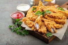 Tiras empanadas del pollo con dos clases de salsas en un tablero de madera Alimentos de preparación rápida en fondo marrón oscuro fotos de archivo libres de regalías