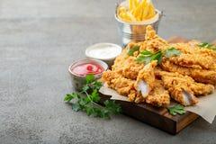 Tiras empanadas del pollo con dos clases de salsas y de patatas fritas en un tablero de madera Alimentos de preparación rápida en imagen de archivo libre de regalías