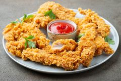 Tiras empanadas del pollo con la salsa de tomate de tomate en una placa blanca Alimentos de preparación rápida en fondo marrón os foto de archivo libre de regalías