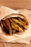 Tiras fritas de la berenjena en el papel y en una tabla de cortar Ajo, especias, salsa de tomate en el plato de cristal en la tab fotos de archivo