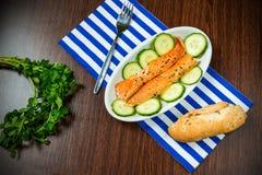 Tiras, pepino y pan del vientre del salmón ahumado en servilleta rayada Fotografía de archivo libre de regalías