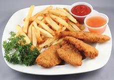 Tiras y fritadas del pollo combinadas Imagen de archivo libre de regalías