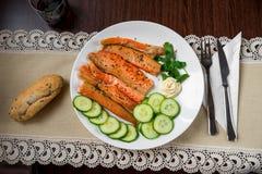 Tiras y pepino del vientre del salmón ahumado en la placa, los cubiertos y el pan blancos en mantel de encaje en la tabla de made Foto de archivo libre de regalías