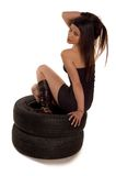 Tire. Young sexy girl sitting on a car wheels Royalty Free Stock Photo